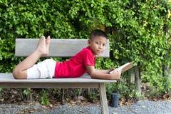Мальчик лежа на руке деревянной скамьи держа смотреть книги Стоковое Изображение