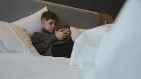 Мальчик лежит на кровати со смартфоном в его руках Сообщение и игры на смартфоне акции видеоматериалы