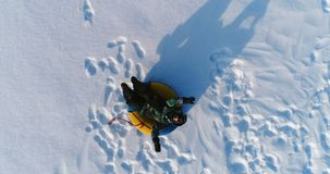 Мальчик 7 лет кладет на трубопровод в снеге Камера медленно поднимая Воздушный отснятый видеоматериал видеоматериал