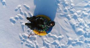 Мальчик 7 лет кладет на трубопровод в снеге Камера медленно причаливая Воздушный отснятый видеоматериал сток-видео