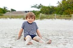 Мальчик маленького ребенка имея потеху на тропическом пляже Стоковое Изображение