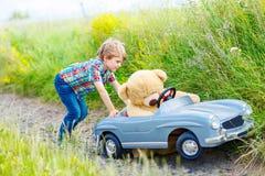 Мальчик маленького ребенка управляя большим автомобилем игрушки с медведем, outdoors стоковые фото