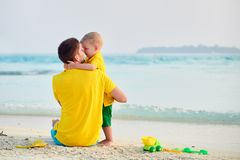 Мальчик малыша на пляже с отцом стоковая фотография