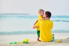 Мальчик малыша на пляже с отцом стоковое фото