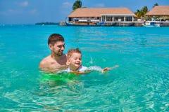 Мальчик малыша учит поплавать с отцом стоковая фотография