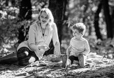 Мальчик мамы и ребенк ослабляя пока пеший туризм в пикнике семьи леса Женщина матери милая и меньший сын сидят на шотландке ослаб стоковое фото