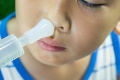 Мальчик моет нос с соляным самостоятельно стоковое изображение rf