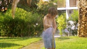 Мальчик моча лужайку и получая влажный сток-видео