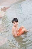 мальчик наслаждаясь бассеином фонтана Стоковые Изображения