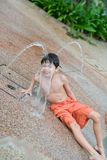мальчик наслаждаясь водой фонтана Стоковое Изображение