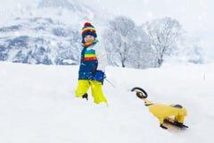 Мальчик наслаждаясь ездой саней Sledding ребенка Ребенк малыша ехать розвальни Игра детей outdoors в снеге  стоковое изображение