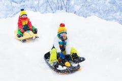 Мальчик наслаждаясь ездой саней Sledding ребенка Ребенк малыша ехать розвальни Игра детей outdoors в снеге  стоковые фотографии rf