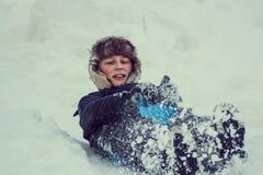 Мальчик наслаждаясь ездой саней Sledding ребенка Ребенк малыша ехать розвальни Дети играют outdoors в снеге Скелетон детей в стоковое фото rf