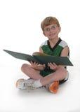 мальчик наслаждаясь детенышами чтения Стоковая Фотография