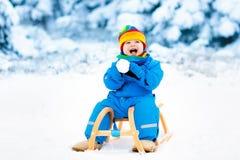 Мальчик на езде саней Sledding ребенка Ребенк с розвальнями Стоковая Фотография