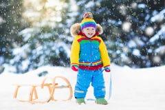 Мальчик на езде саней Sledding ребенка Ребенк с розвальнями Стоковые Фото