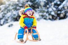 Мальчик на езде саней Sledding ребенка Ребенк с розвальнями Стоковое Изображение