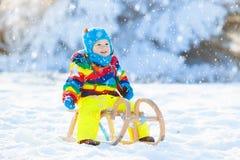 Мальчик на езде саней Sledding ребенка Ребенк с розвальнями Стоковое Фото