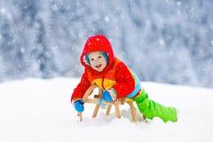 Мальчик на езде скелетона Sledding ребенка Ребенк на розвальнях стоковые фото
