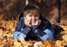 Мальчик на листьях осени Стоковое Фото