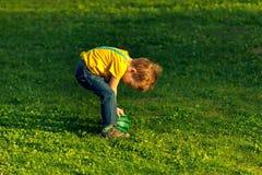 Мальчик на лужайке зеленой травы в парке лета, счастливом стоковое изображение