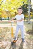 Мальчик на оранжевом скутере стоковое фото