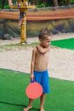 Мальчик на пляже играя теннис пляжа стоковая фотография rf
