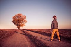 Мальчик на сельской дороге с деревом на горизонте Стоковая Фотография
