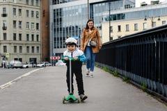 Мальчик на скутере в городе с его матерью стоковое фото rf