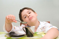 Мальчик на таблице с ложкой Стоковая Фотография RF