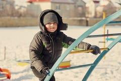 Мальчик на холодный день на спортивной площадке Стоковое фото RF