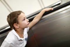 Мальчик на эскалаторе стоковая фотография rf
