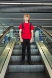 Мальчик на moving лестнице Стоковая Фотография