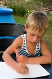 мальчик немногая изучает для писания стоковое изображение