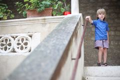 Мальчик не стоит на верхнем шаге лестницы Стоковые Фотографии RF
