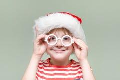 Мальчик носит стекла и шляпу ` s Санты Портрет Стоковое Изображение
