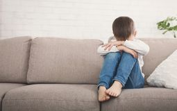 Мальчик обнимая его колено в разрыве, сидя на софе стоковое изображение