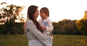 Мальчик обнимая мать на заходе солнца в лете, любящем сыне и счастливом касаться семьи сток-видео