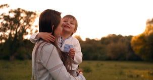 Мальчик обнимая мать на заходе солнца в лете, любящем сыне и счастливом касаться семьи акции видеоматериалы