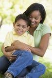 мальчик обнимая outdoors сь детенышей женщины Стоковые Изображения