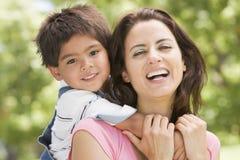 мальчик обнимая outdoors сь детенышей женщины Стоковое фото RF
