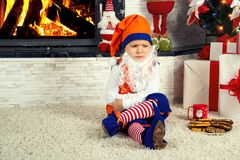 Мальчик одетый как эльф рождества сидит и уныл под деревом и ждет Санту Стоковые Фото