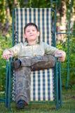Мальчик отдыхает в deckchair стоковая фотография rf