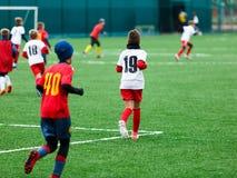 Мальчик пинает футбольный мяч Мальчик бежит после шарика на зеленой траве футболист в белой и красной рубашке мальчики капая стоковые фото