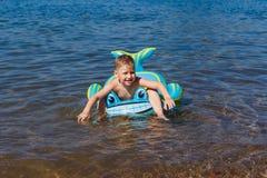 Мальчик плавает на резиновый дельфина в море стоковые изображения rf