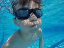 Мальчик плавает под водой в бассейне стоковая фотография rf