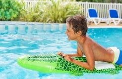Мальчик плавая на раздувную игрушку в бассейне Стоковая Фотография RF