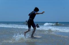 мальчик пляжа учя прибой к Стоковые Изображения