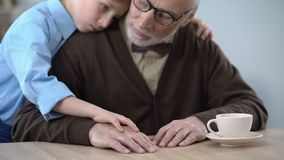 Мальчик поддерживая унылый деда, обнимая для того чтобы утешить его, заботу семьи видеоматериал