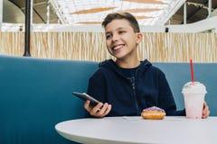 Мальчик подростка сидит на таблице в кафе, выпивает milkshake, ест донут, держит smartphone в его руке Мальчик играет передвижные Стоковая Фотография